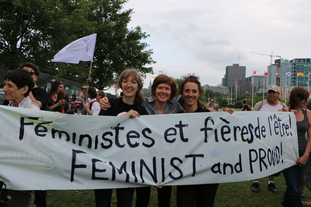 "three women holding a banner ""Feminist and proud"""