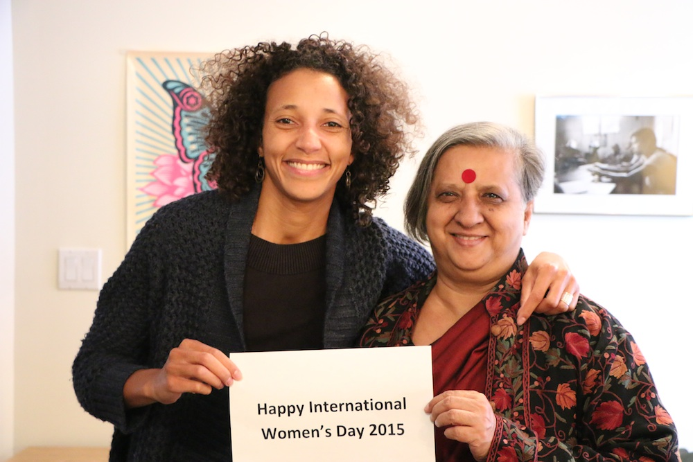 Patricia and Khushi holding a Happy International Women's Day sign