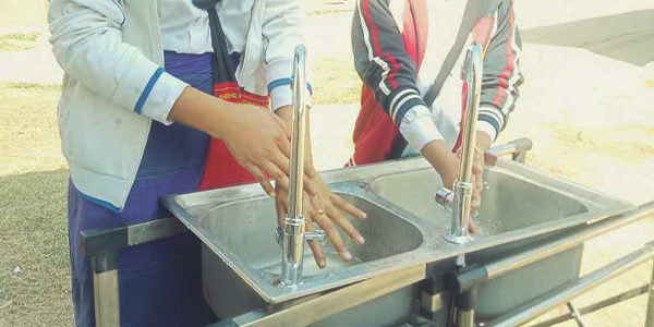Two Burmese youth wash their hands at a basin. The water is flowing from the taps.