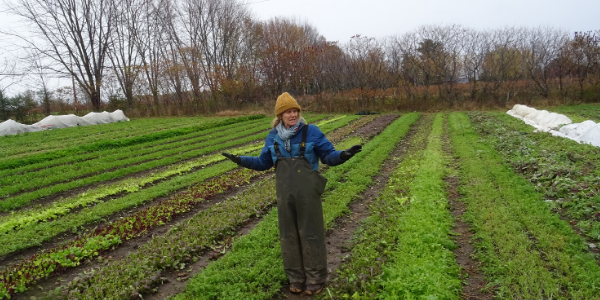 A woman farmer stands in her field, arms outstretched. She is wearing overalls and a hat. At her feet are rows of growing crops.