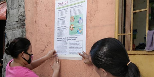 Two Likhaan health workers tape an informational poster to the side of a building. The poster has information about preventing the spread of COVID-19. One of the women is wearing a face mask.