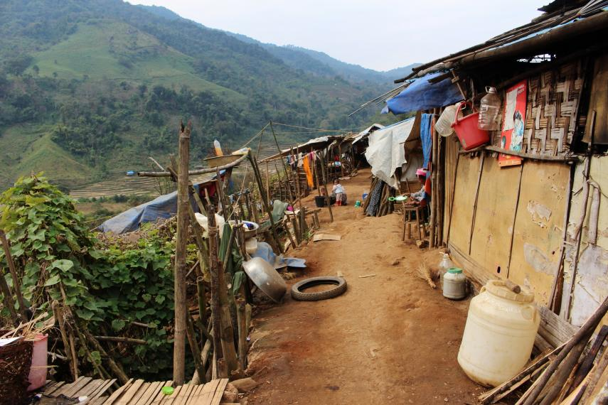 shacks for refugees on right, dirt path down the middle and cliff down to hills on left