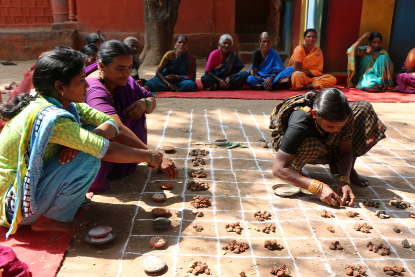 Women crouch outside over a grid drawn with chalk as they place seeds within the squares. The women are wearing colourful saris.