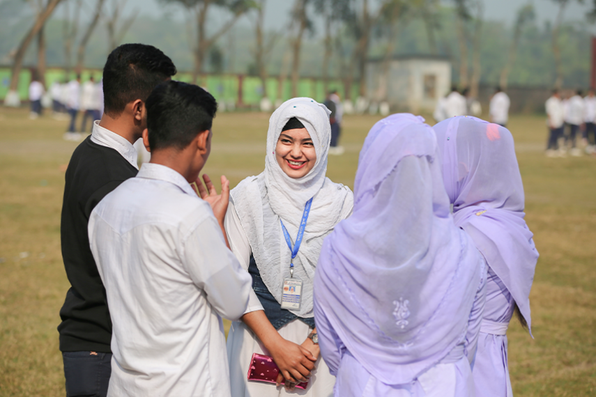 Sanjida Akhter stands in a schoolyard with her hands folded in front of her body, smiling at a group of classmates who stand around her in a circle.