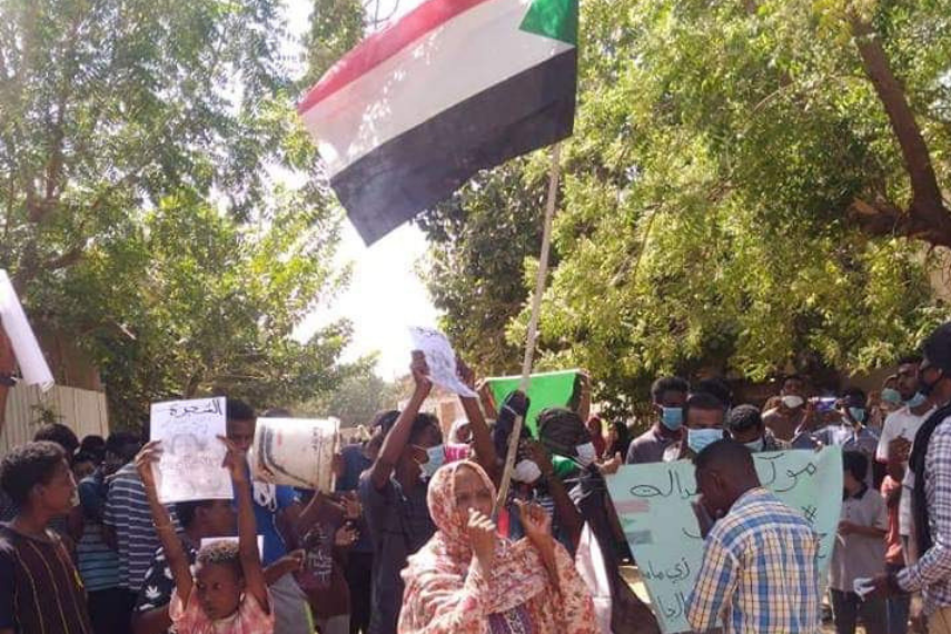 A woman holding a Sudanese flag speaks into a megaphone. She is surrounded by protesters.