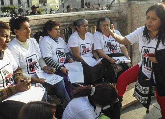 """A man doesn't rape"": María Ysabel Cedano (far right) speaking to fellow activists to mobilize around women's violence."