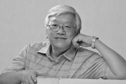 Martin Khor sits for the camera, resting his cheek on one hand. The photo is black and white.