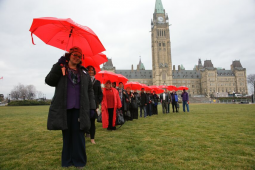 Medicare advocates on Parliament Hill in Ottawa with red umbrellas