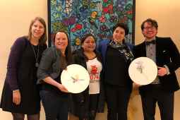 28.Representatives from the National Aboriginal Council of Midwives and Clinic 554 stand with their 2019 Peter Gillespie Social Justice Award plaques and Peruvian activist Maria Ysabel Cedano. In the background is colourful Indigenous artwork.
