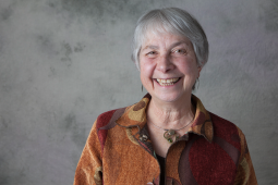 1.Sari Tudiver smiles brightly at the camera. She is wearing an orange patterned shirt and has short, close-cropped grey hair. Behind her is a grey background.