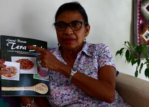 Augusta Henriques avec le livre de recettes de Tiniguena, qui valorise les ingrédients et saveurs traditionnellement guinéens.