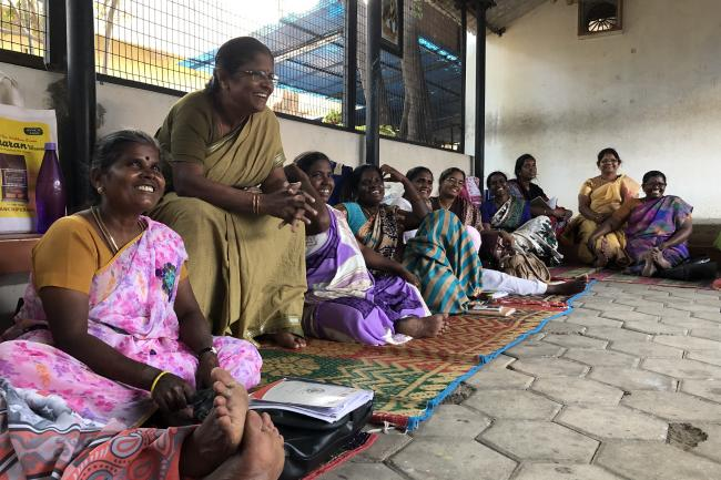 Women representatives of Tamil Nadu Women's Collective sit in a circle, sharing and laughing.