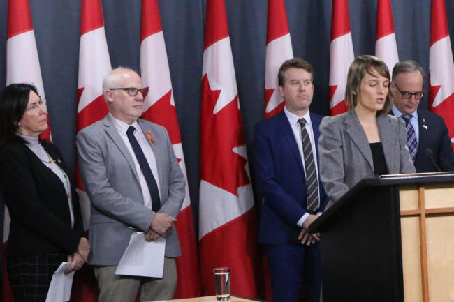 Samantha McGavin joins Amnesty's Alex Neve and Kyle Matthews of the Montreal Institute for Genocide and Human Rights Studies in pressing for stronger Canadian measures. Also on stage: MPs Cheryl Hardcastle (at left) and Rob Oliphant (at right).