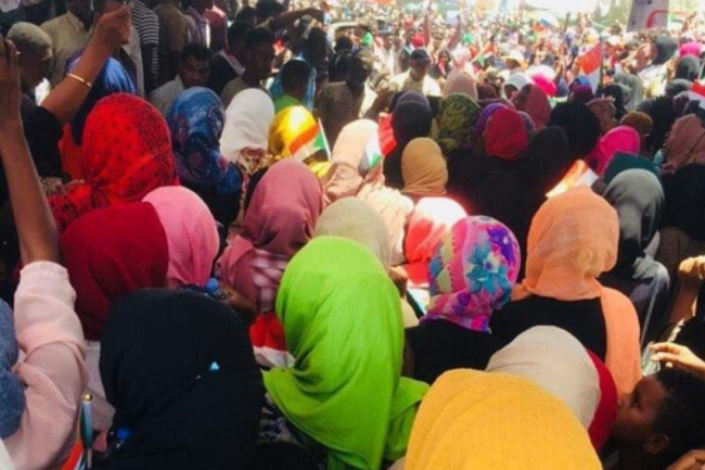 A group of Sudanese women gathered in protest with their backs to the camera